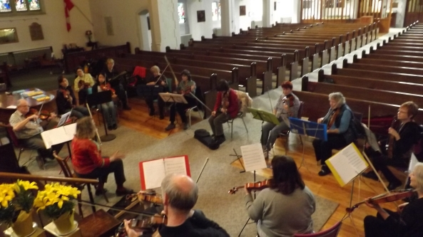 Group of about 20 fiddlers seated in a circle around Anne Lederman.
