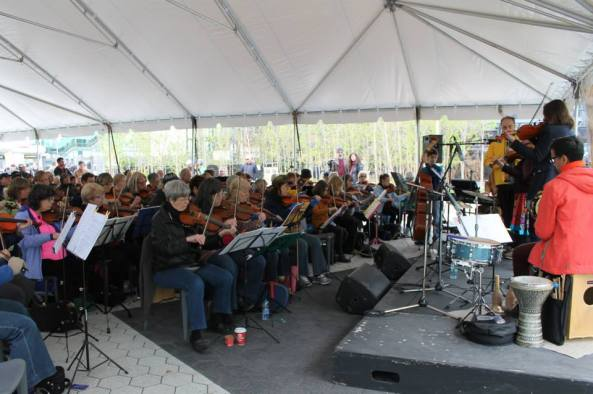 73 fiddlers facing the stage underneath a canopy at Harbourfront with a large audience behind them.