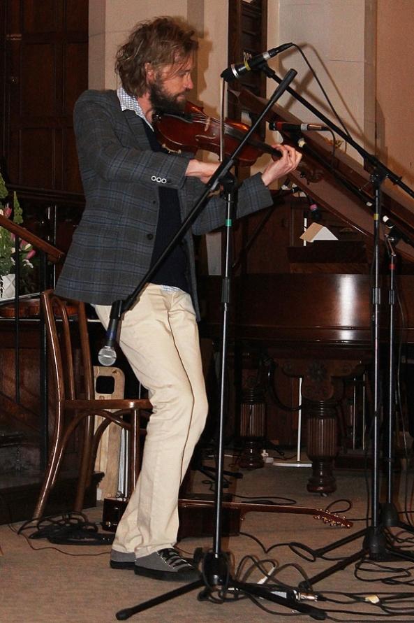 Jake Pilatzke 'steppin' and fiddling on stage.