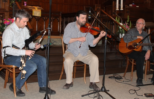 Musician from North Atlantic Drift on stage: Piper Ross Griffiths, fiddler Dan MacDonald, and tenor banjo/guitar maestro Brian Taheny.