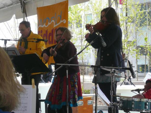 Martin Vendeven, Anne Lederman and Leah leading the fiddlers on stage under the canopy at Harbourfront.